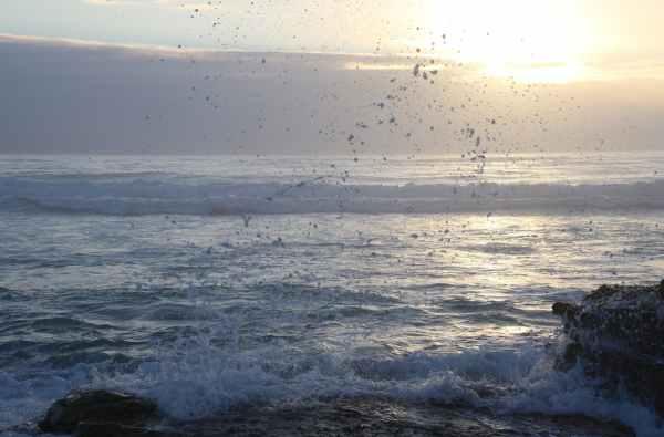ocean waves hammering rock boulder