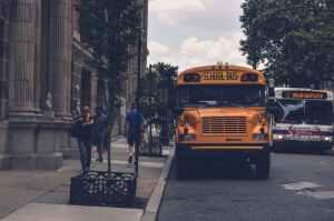 yellow school bus beside gray concrete building