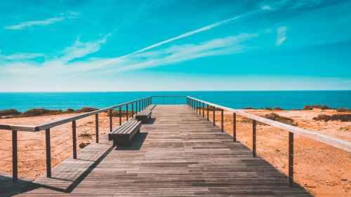 beach bench boardwalk clouds