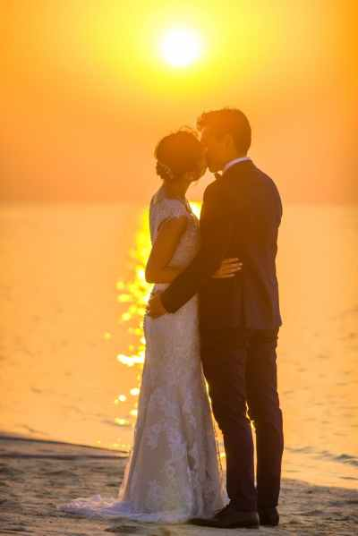 man and woman kissing under sunset