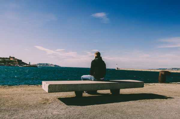 person wearing blue jeans sitting on bench