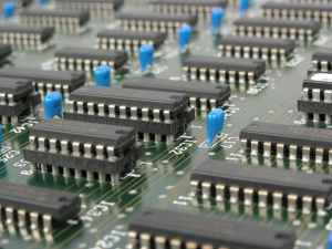 black and blue electronic tools on green circuit board