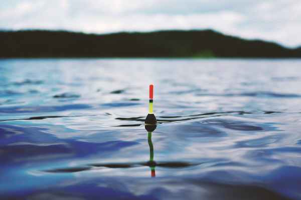 red yellow and black bouy on body of water during daytime
