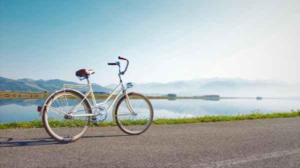 gray commuter bike parked on road beside sea