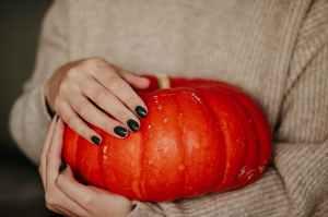 photo of woman holding a pumpkin