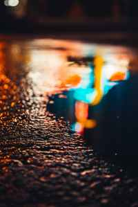 water droplets on black asphalt road during night time