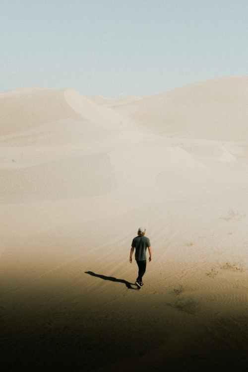 photo of person walking on desert